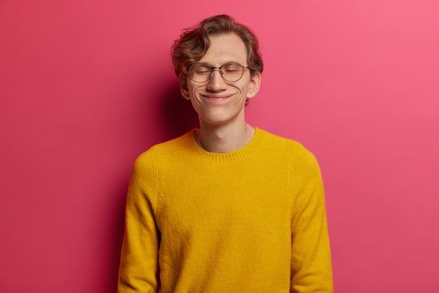 Portret van knappe man sluit ogen met plezier, blij om lovende woorden van werkgever te horen, heeft een grappig gezicht, draagt een grote optische bril en een gele trui, stopt nooit met dromen, staat opgelucht
