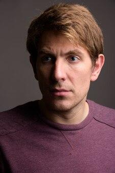 Portret van knappe man tegen grijze muur