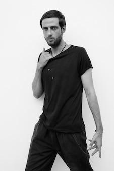 Portret van knappe man tegen witte muur buiten in zwart-wit