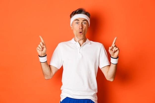 Portret van knappe man van middelbare leeftijd in sportkleding, vingers omhoog
