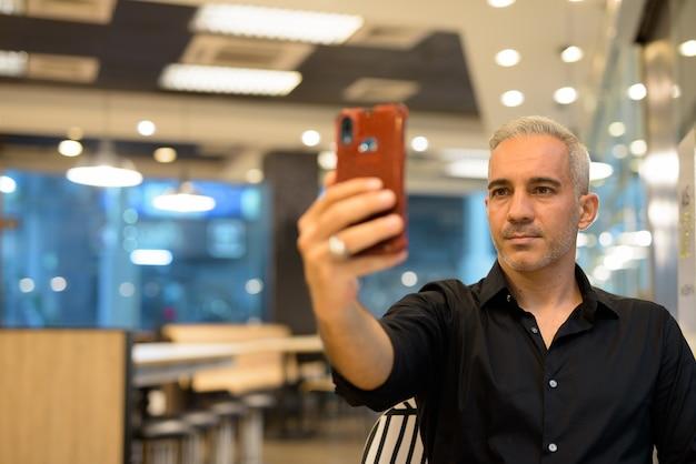 Portret van knappe man zit in coffeeshop met behulp van mobiele telefoon