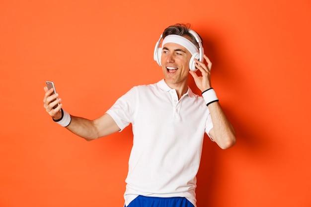 Portret van knappe mannelijke atleet van middelbare leeftijd, die gymnastiekuniform draagt