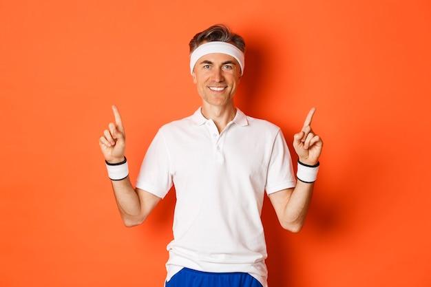 Portret van knappe, mannelijke atleet van middelbare leeftijd glimlachen, vingers omhoog