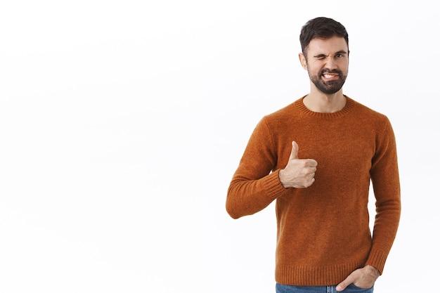 Portret van knappe mannelijke bebaarde man verzekert goede kwaliteit, beveelt item aan, knipoogt en glimlacht als duim omhoog, keurt goed en gaat akkoord, verzekert alles onder controle, witte muur