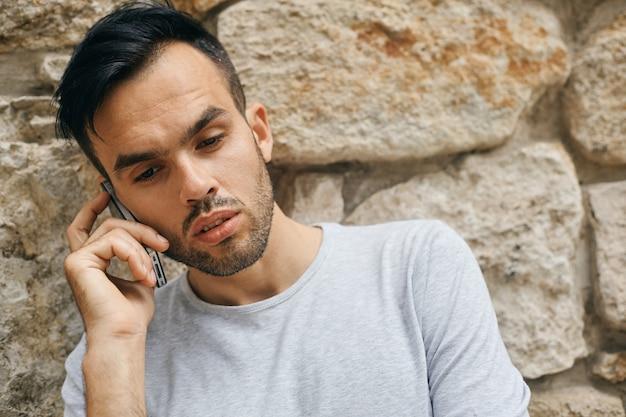 Portret van knappe mannelijke student buiten op de universiteitscampus en praten op mobiele telefoon, kopieer ruimte