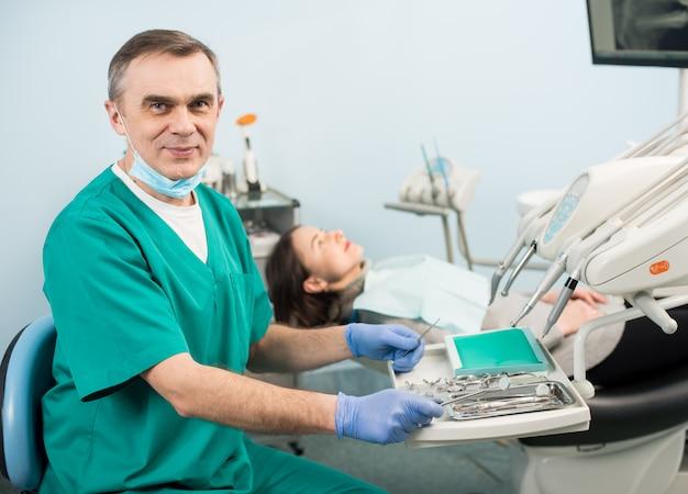 Portret van knappe mannelijke tandarts met tandheelkundige apparaten in de tandheelkundige kliniek. vrouwelijke patiënt. tandheelkunde