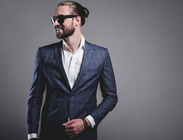 Portret van knappe mode stijlvolle hipster zakenman model gekleed in elegant blauw pak in zonnebril die zich voordeed op grijs