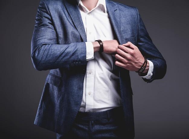 Portret van knappe mode stijlvolle hipster zakenman model gekleed in elegant blauw pak op grijs