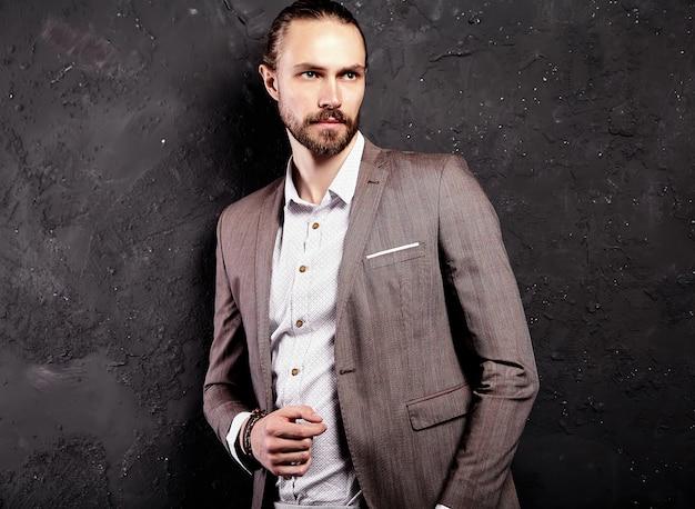 Portret van knappe mode stijlvolle hipster zakenman model gekleed in elegant bruin pak in de buurt van donkere muur