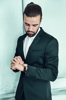 Portret van knappe mode stijlvolle hipster zakenman model gekleed in elegant zwart pak.