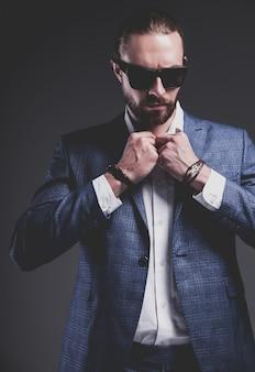 Portret van knappe mode stijlvolle hipster zakenman model gekleed in elegante blauwe pak poseren op grijs