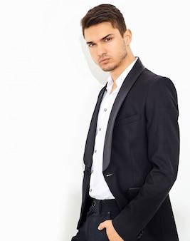 Portret van knappe mode stijlvolle zakenman model gekleed in elegante zwarte klassieke pak poseren. metrosexual