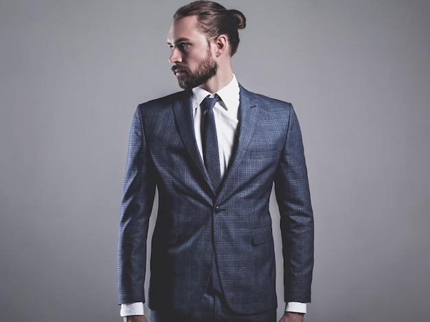 Portret van knappe mode zakenman model gekleed in elegant blauw pak met bril die zich voordeed op grijs