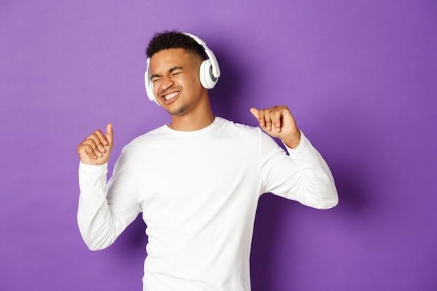 Portret van knappe moderne kerel, muziek in hoofdtelefoons luisteren en zorgeloos dansen
