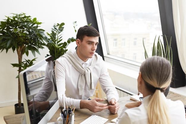 Portret van knappe nerveuze jonge brunette mannelijke kandidaat beantwoorden van vragen van onherkenbare vrouwelijke human resources-specialist tijdens sollicitatiegesprek, zittend aan een bureau in modern kantoor interieur.