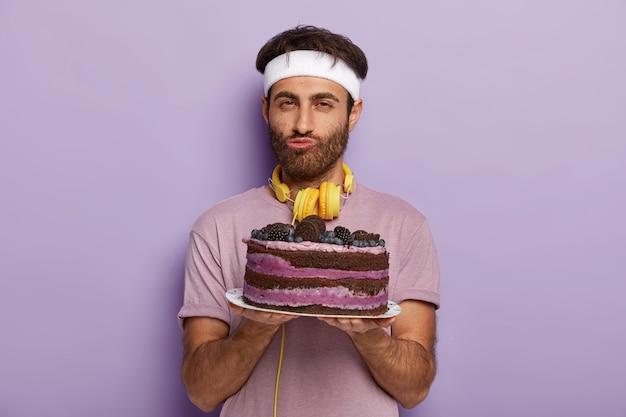 Portret van knappe ongeschoren man houdt heerlijke cake op plaat, gekleed in vrijetijdskleding, heeft goede wil om geen dessert staat tegen paarse muur te eten, geniet van goede smaak. mannetje met zoete schotel