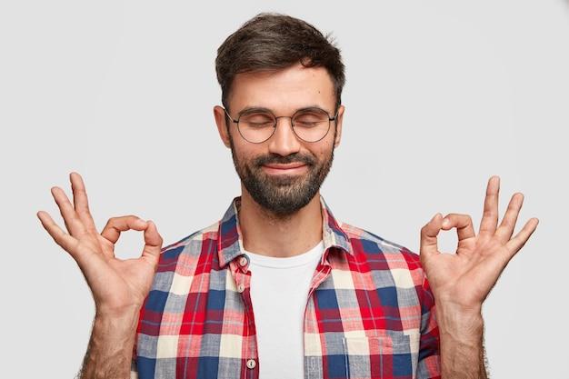 Portret van knappe ongeschoren man toont oke of als gebaar met beide handen, lacht aangenaam, houdt de ogen dicht