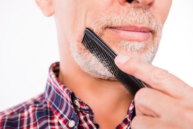 Portret van knappe oude man zijn baard kammen close-up