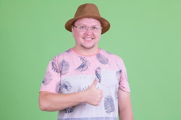 Portret van knappe overgewicht bebaarde toeristische man tegen chromakey of groene muur Premium Foto