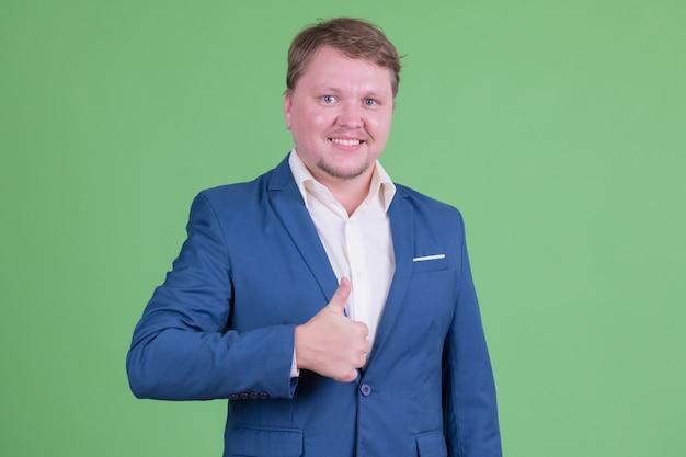 Portret van knappe overgewicht bebaarde zakenman pak dragen tegen chromakey of groene muur