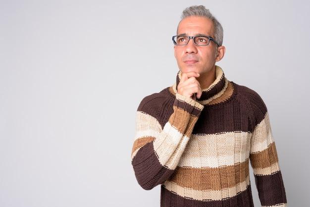 Portret van knappe perzische man denken met bril klaar voor de winter