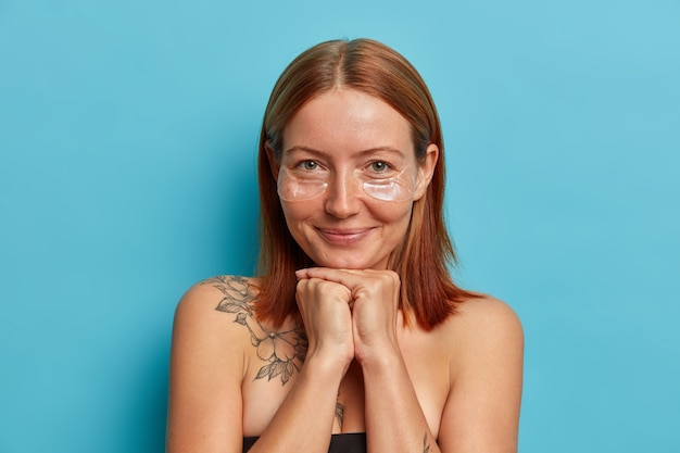 Portret van knappe roodharige vrouw met sproeten houdt de handen onder de kin, past transparante collageenpleisters toe onder de ogen, hydrateert de huid en verwijdert rimpels, vormt met blote schouders