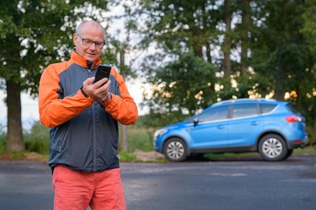 Portret van knappe senior man langs de kant van de weg in het bos