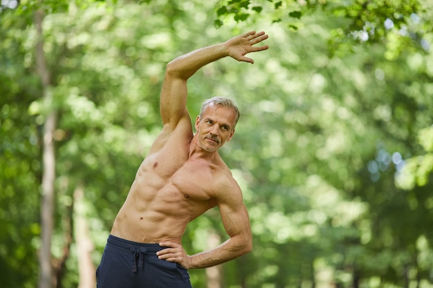 Portret van knappe senior sportman met goed gespierd lichaam topless staan ergens in park rekoefening doen