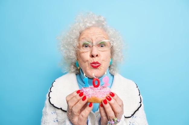 Portret van knappe senior vrouw die kaarsen gaat blazen op donut viert 102e verjaardag ziet er mooi uit heeft rode manicure lichte make-up gekleed in trui