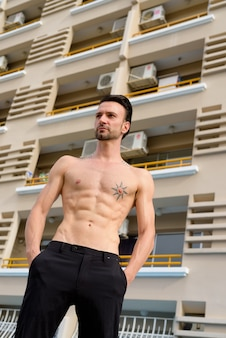 Portret van knappe shirtloze man buitenshuis met sixpack buikspieren en tatoeages