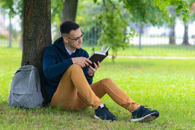Portret van knappe slimme student buiten in groen park