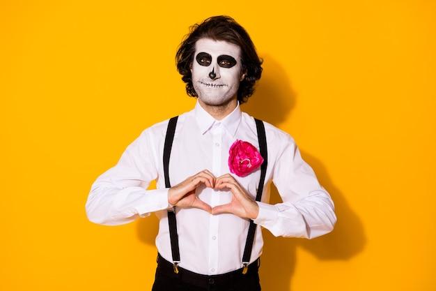 Portret van knappe spookachtige griezelige vrolijke amoureuze aanhankelijke kerel heer zombie tonen hart vorm romantiek gevoelens cupido amour geïsoleerd helder levendig glans levendige gele kleur achtergrond