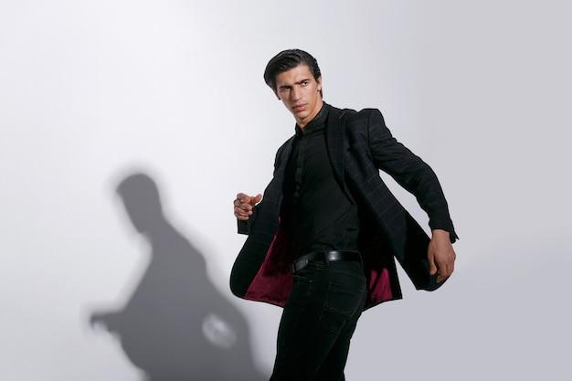 Portret van knappe sterke jonge man in stijlvol zwart pak, geïsoleerd op een witte achtergrond. horizontale weergave.