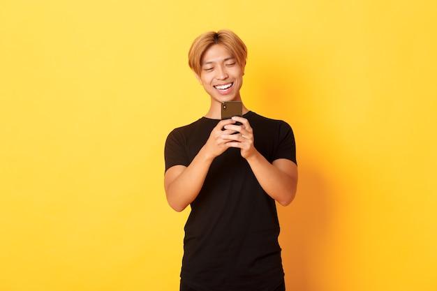 Portret van knappe stijlvolle aziatische man met blond haar, met behulp van mobiele telefoon en glimlachen