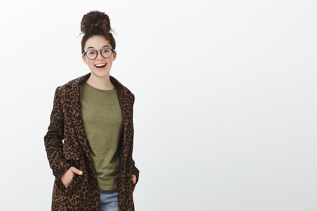 Portret van knappe stijlvolle europese vrouw met krullend haar en knot kapsel, zwarte trendy bril en luipaard jas dragen, hand in hand in de zakken en breed glimlachend