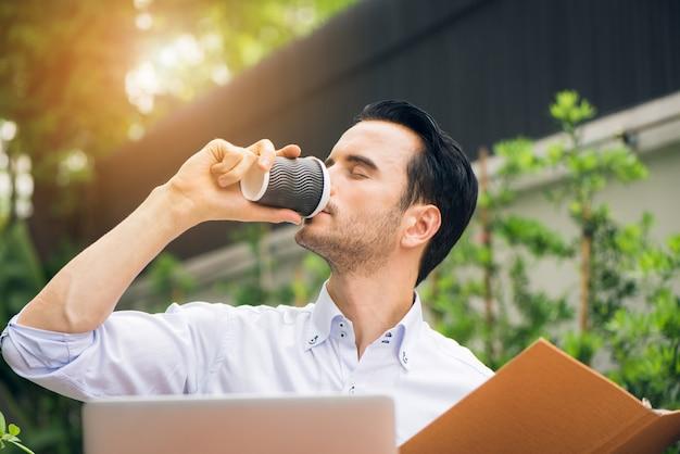 Portret van knappe succesvolle man drinkt koffie. de gelukkige mens neemt koffiepauze aangezien hij bij zijn laptop zit die van huisbureau met boekenkast werkt. zakenman ontbijten buiten zitten