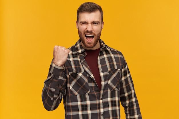 Portret van knappe, succesvolle man met donkerbruin haar en varkenshaar. een geruit overhemd en accessoires dragen. heft vuist in viering, geïsoleerd over gele muur