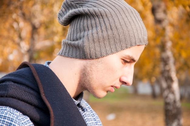 Portret van knappe tiener met wollen hoed in het park