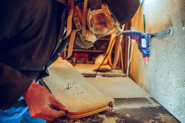 Portret van knappe timmerman werken met houten skate op workshop, profiel te bekijken