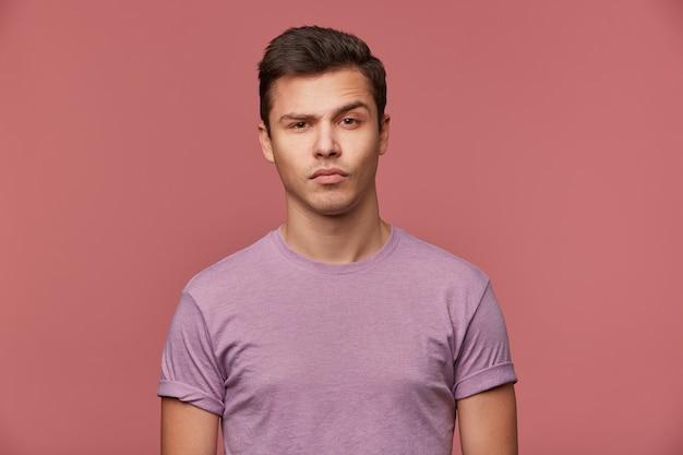 Portret van knappe twijfelende jongeman draagt in leeg t-shirt, kijkt naar de camera met opgetrokken wenkbrauw, staat op roze achtergrond.
