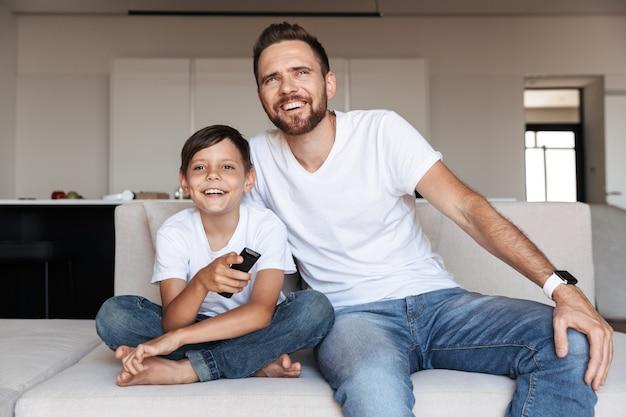 Portret van knappe vader en zoon glimlachen, zittend op de bank binnen met afstandsbediening