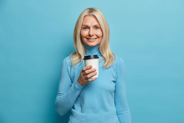 Portret van knappe volwassen europese vrouw houdt wegwerp kopje koffie