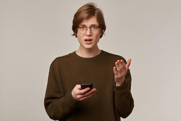 Portret van knappe, volwassen man met blond haar. bruine trui en bril dragen.