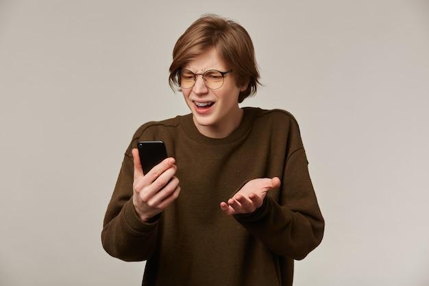Portret van knappe, volwassen man met blond haar. hij draagt een bruine trui, een bril en heeft beugels. stand geïsoleerd over grijze muur