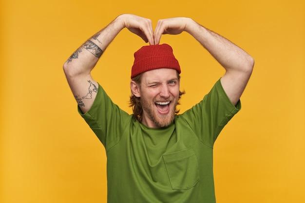 Portret van knappe, volwassen man met blond kapsel en baard. het dragen van een groen t-shirt en een rode muts. heeft tatoeages. hart ondertekenen met handen. geïsoleerd over gele muur