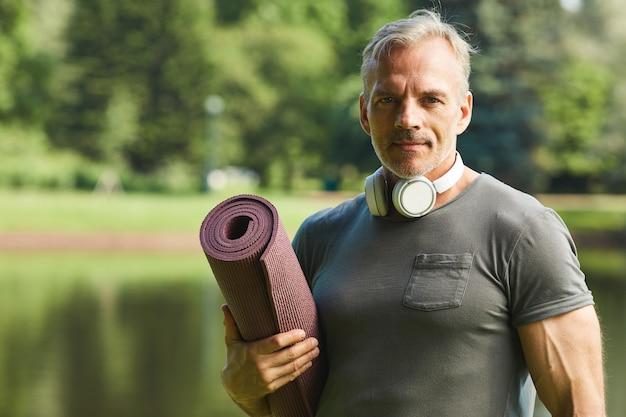 Portret van knappe volwassen man met draadloze koptelefoon om nek met warmgewalste fitness mat in stadspark