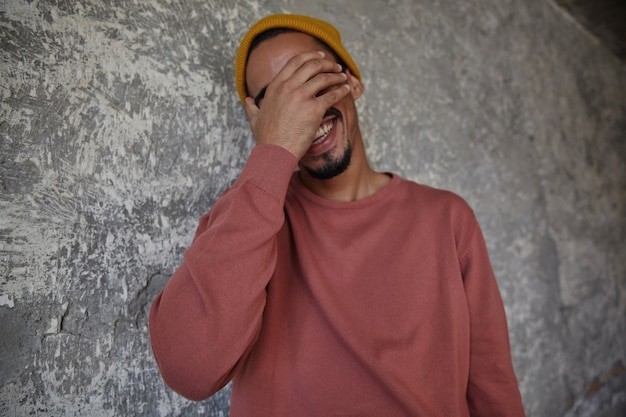 Portret van knappe vrolijke bebaarde man met donkere huid met opgeheven hand op zijn gezicht en gelukkig lachen, aangenaam verrast