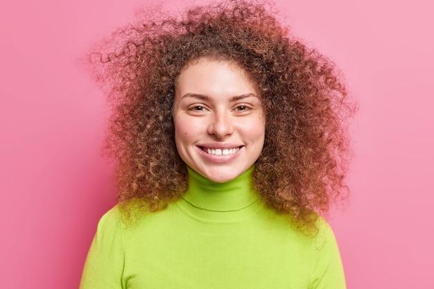 Portret van knappe vrolijke europese vrouw met krullend borstelig haar glimlacht breed gekleed in groene coltrui geïsoleerd over roze muur. zorgeloos lachende europese vrouw geniet van vrije tijd