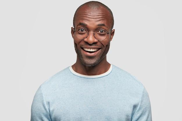 Portret van knappe vrolijke jonge kale man met blije uitdrukking, toont witte zelfs perfecte tanden
