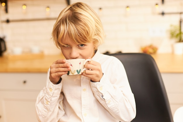Portret van knappe vrolijke jongen met blond haar, het drinken van thee tijdens het ontbijt voor school, kopje houden en lachend met keukengerei en slinger op aanrecht